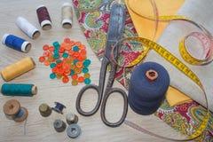 Las tijeras y el equipo de costura incluye los hilos de diversos colores, del dedal y de otros accesorios de costura en la tabla  Fotografía de archivo libre de regalías