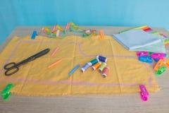 Las tijeras y el equipo de costura incluye los hilos de diversos colores, del dedal y de otros accesorios de costura en la tabla  Imagenes de archivo