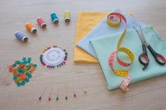 Las tijeras y el equipo de costura incluye los hilos de diversos colores, del dedal y de otros accesorios de costura en la tabla  Imagen de archivo