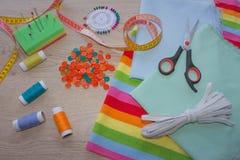 Las tijeras y el equipo de costura incluye los hilos de diversos colores, del dedal y de otros accesorios de costura en la tabla  Foto de archivo