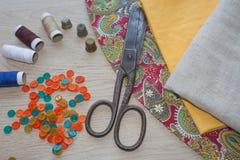 Las tijeras y el equipo de costura incluye los hilos de diversos colores, del dedal y de otros accesorios de costura en la tabla  Fotos de archivo libres de regalías