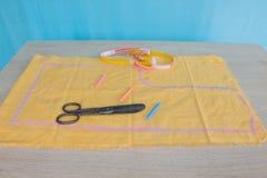 Las tijeras y el equipo de costura incluye los hilos de diversos colores, del dedal y de otros accesorios de costura en la tabla  Fotografía de archivo
