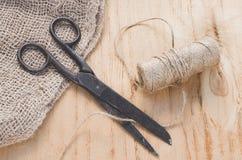 Las tijeras y el yute viejos de la madeja trenzan en un fondo de madera, foco selectivo, estilo rústico imagen de archivo