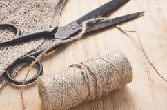 Las tijeras y el yute viejos de la madeja trenzan en un fondo de madera, foco selectivo, estilo rústico fotos de archivo