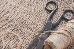Las tijeras y el yute viejos de la madeja trenzan en una arpillera imagen de archivo