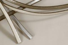 Las tiras de cuero atan adorno en blanco y negro en fondo de cuero en colores pastel Imágenes de archivo libres de regalías
