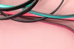 Las tiras de cuero atan adorno en colores vivos en fondo de cuero en colores pastel rosado Foto de archivo
