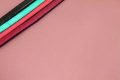 Las tiras de cuero atan adorno en colores vivos en fondo de cuero en colores pastel rosado Fotos de archivo