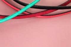 Las tiras de cuero atan adorno en colores vivos en fondo de cuero en colores pastel rosado Fotografía de archivo