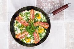 Las tiras de tocino deliciosas, las salchichas y los huevos fritos desayunan en cacerola Fotos de archivo libres de regalías