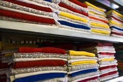 Las toallas del hotel y ropa de cama frescas se apilan en el estante imagenes de archivo
