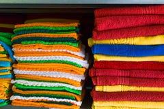 Las toallas frescas del hotel doblaron y apilaron en un estante fotos de archivo