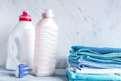 Las toallas llenan con las botellas detergentes y plásticas en maqueta del lavadero fotografía de archivo