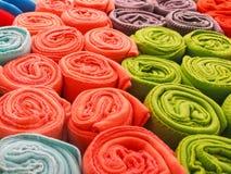 Las toallas multicoloras rodaron en una mentira del tubo en uno a en el estante La tela multicolora rodó en un tubo foto de archivo libre de regalías