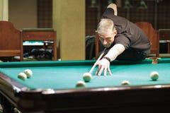 Las tomas del jugador tienen como objetivo la bola en billares Fotografía de archivo