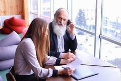 Las tomas jubiladas los hombres de negocios experimentados llaman en el teléfono y las partes a Fotografía de archivo libre de regalías