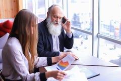 Las tomas jubiladas los hombres de negocios experimentados llaman en el teléfono y las partes a Fotos de archivo libres de regalías