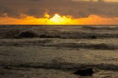 Las tonalidades anaranjadas de la puesta del sol reflejaron en las ondas Imagen de archivo