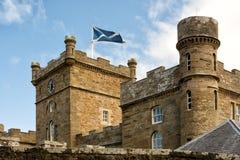 Las torres de Calzean se escudan con la bandera escocesa que agita en la brisa Imagen de archivo libre de regalías