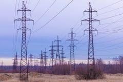 Las torres de la tubería eléctrica en el campo del campo en el fondo del cielo azul y del bosque fotos de archivo