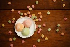 Las tortas de arroz de Mochi en la placa blanca con el caramelo colorido de la fruta caen Imagen de archivo libre de regalías