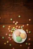 Las tortas de arroz de Mochi en la placa blanca con el caramelo colorido de la fruta caen Foto de archivo libre de regalías