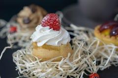 Las tortas divinas con las frambuesas y la crema, el fondo se empañan con el otro cak fotografía de archivo libre de regalías