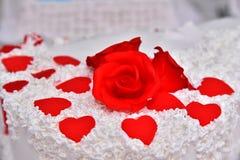 Las tortas dulces bajo la forma de rosas rojas adornan el pastel de bodas con ramitas más decorativas de la crema blanca Foto de archivo libre de regalías