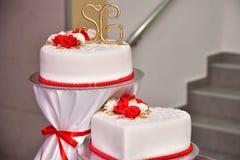 Las tortas dulces bajo la forma de rosas rojas adornan el pastel de bodas con ramitas más decorativas de la crema blanca Fotografía de archivo