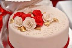Las tortas dulces bajo la forma de rosas rojas adornan el pastel de bodas con ramitas más decorativas de la crema blanca Imagen de archivo