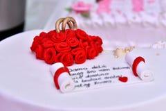 Las tortas dulces bajo la forma de rosas rojas adornan el pastel de bodas con ramitas más decorativas de la crema blanca Imagen de archivo libre de regalías
