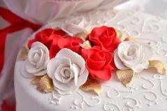 Las tortas dulces bajo la forma de rosas rojas adornan el pastel de bodas con ramitas más decorativas de la crema blanca Fotos de archivo libres de regalías