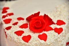 Las tortas dulces bajo la forma de rosas rojas adornan el pastel de bodas con ramitas más decorativas de la crema blanca Fotografía de archivo libre de regalías