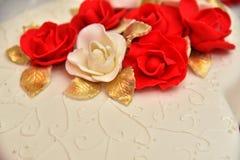 Las tortas dulces bajo la forma de rosas rojas adornan el pastel de bodas con ramitas más decorativas de la crema blanca Imagenes de archivo