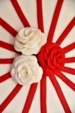 Las tortas dulces bajo la forma de rosas rojas adornan el pastel de bodas con ramitas más decorativas de la crema blanca Foto de archivo