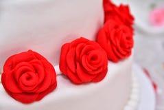 Las tortas dulces bajo la forma de rosas rojas adornan el pastel de bodas con ramitas más decorativas de la crema blanca Fotos de archivo