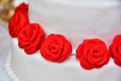 Las tortas dulces bajo la forma de rosas rojas adornan el pastel de bodas con ramitas más decorativas de la crema blanca Imágenes de archivo libres de regalías