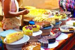 Las tortas sabrosas dulces en la exhibición en los pasteles atascan, en el mercado callejero de la noche Fotografía de archivo libre de regalías