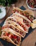 Las tortillas hechas en casa con el pollo, las verduras y la salsa picantes sumergen en la tabla de madera foto de archivo libre de regalías
