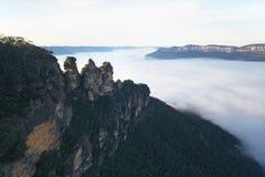 Las tres hermanas rodeadas por la niebla de la mañana Imagenes de archivo