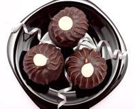 Las tres tortas de chocolate en la placa Imágenes de archivo libres de regalías