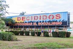LAS TUNAS, CUBA - JAN 27, 2016: Propaganda billboard at Plaza de la Revolucion Square of the Revolution in Las Tunas. It says: Decided to prefect the socialism royalty free stock images