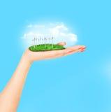 Las turbinas de viento en prado se sostienen en la mano de la mujer contra el cielo azul Imagen de archivo