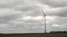 Las turbinas de viento hacen girar en el fondo de nubes oscuras metrajes