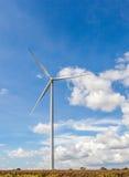 Las turbinas de viento (molinoes de viento) contra el cielo azul nublado y de oro Imagen de archivo