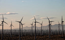 Las turbinas de viento se sientan en una montaña distante en el amanecer Foto de archivo