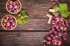 Las uvas agrupan con las hojas en fondo de madera rústico Visión superior imagen de archivo libre de regalías