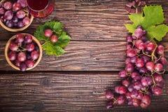 Las uvas agrupan con las hojas y la copa de vino en una vieja parte posterior de madera imagen de archivo libre de regalías