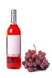 Las uvas agrupan y la botella de vino Fotos de archivo