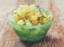 Las uvas blancas en un cuenco verde en el viejo tablero de madera rústico se agrietaron Foto de archivo libre de regalías